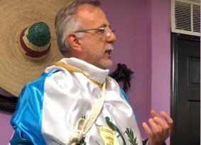 Iván Velásquez da un discurso a migrantes  envuelto en una bandera de Guatemala